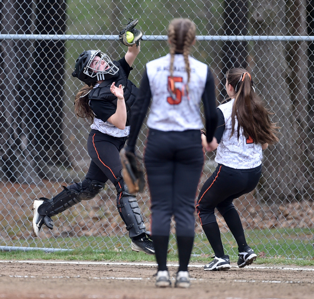 Winslow catcher Cassie Demers, left, makes a catch on a foul ball against Nokomis on Thursday in Winslow.