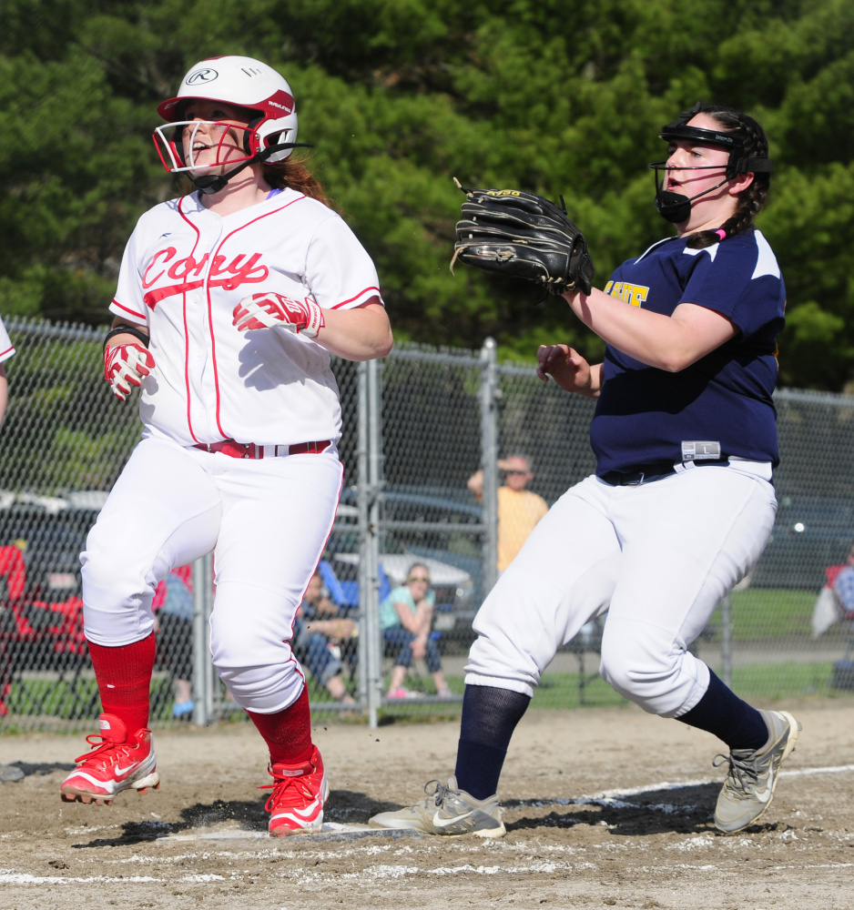 Cony's Cari Hopkins, left, scores on a wild pitch ahead of Mt. Blue pitcher Ellie DeCarolis, who was running in to cover home plate, Friday at Newman Brann Memorial Field in Augusta.