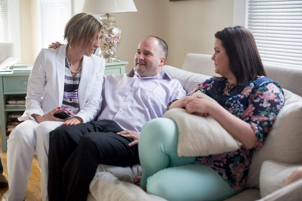 Anthony Sanborn sits on the couch at the home of his friend Lisa Alexander with his wife, Michelle Sanborn, left, and his daughter, Santana Levier, about an hour after leaving the Cumberland County Jail.