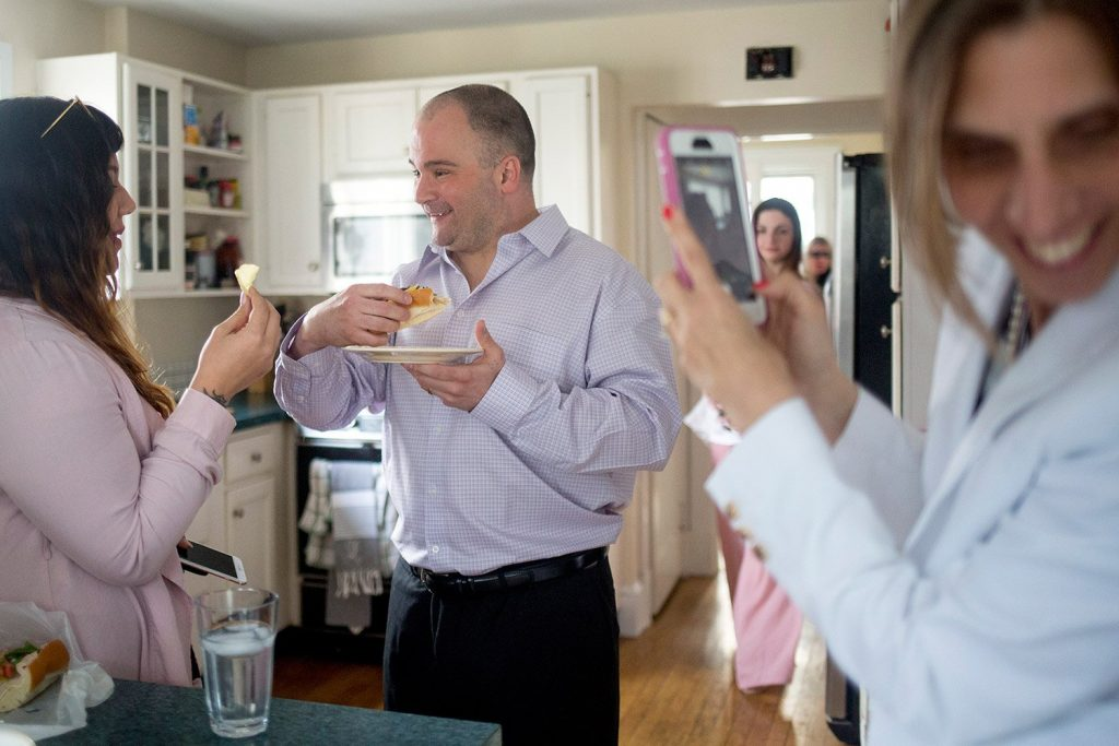 Anthony Sanborn talks with his stepdaughter, Cassie Thanephonesy, as he eats his first meal outside prison – an Italian sandwich – while his wife, Michelle Sanborn, takes a photo.