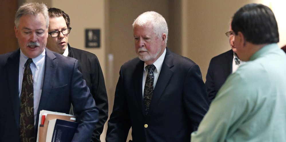 Arthur Peekel, center, a former admissions officer at Phillips Exeter Academy, follows his lawyer Philip Utter, left, past reporters after a court hearing Friday in Brentwood, N.H.
