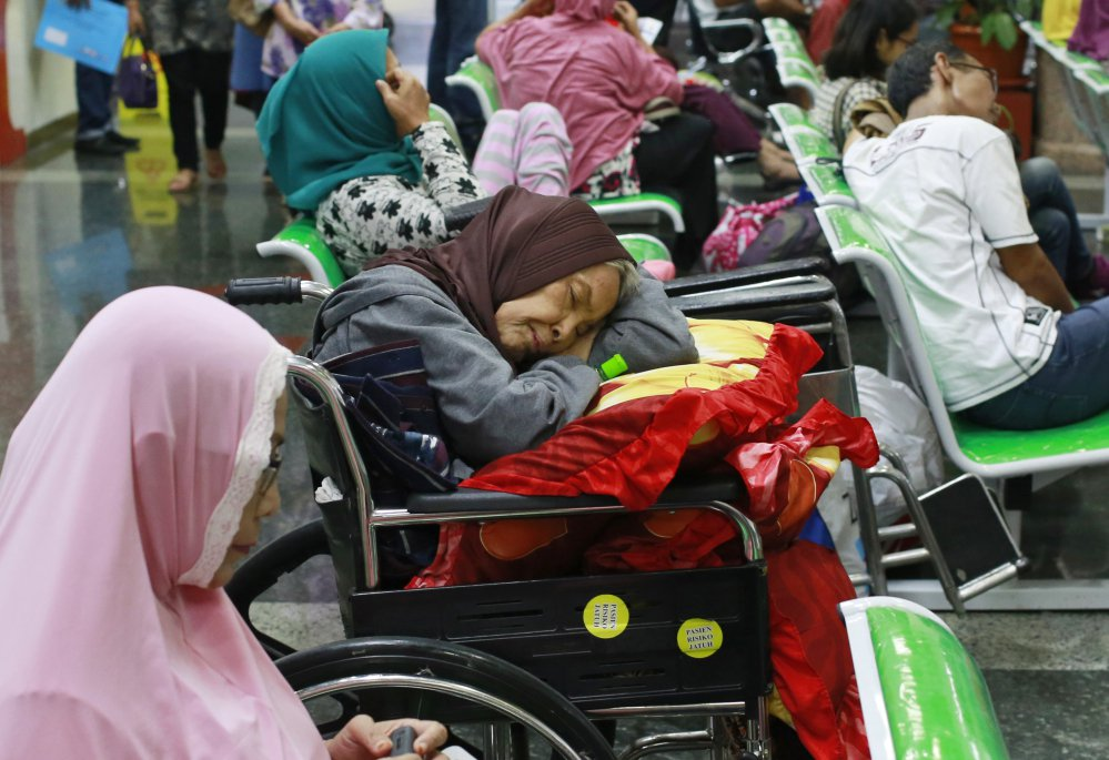 A patient takes a nap on her wheelchair as she waits with others at the registration desk at Dharmais Cancer Hospital in Jakarta, Indonesia, on Monday. A global cyber extortion scheme created chaos in 150 countries and could wreak even greater havoc as more malicious variations appear.