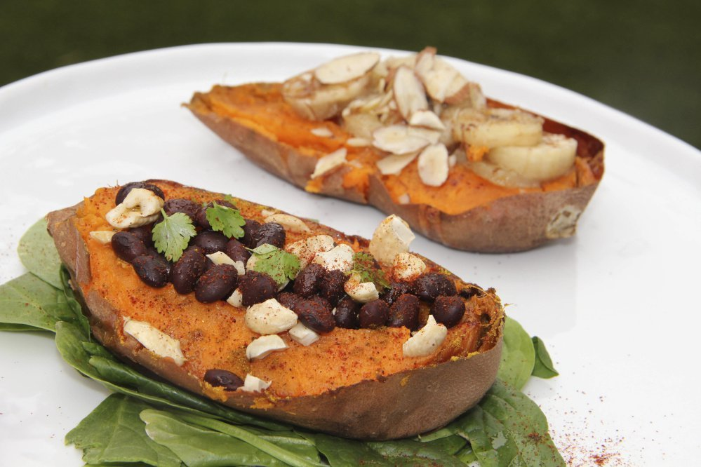 Two halves of a sweet potato prepared with savory and sweet toppings.