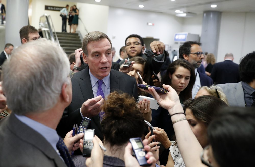 Sen. Mark Warner, D-Va., is surrounded by reporters as he walks on Capitol Hill in Washington on Wednesday. The top Democrat on the Intelligence Committee, Warner said the panel invited former FBI director James Comey to testify in open and closed sessions.