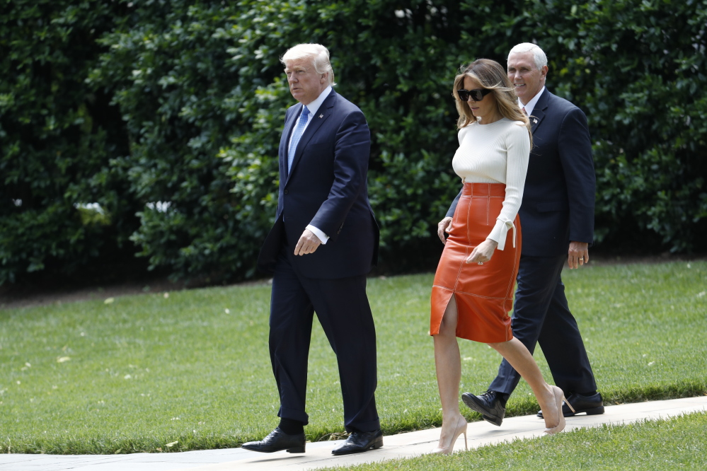 President Trump and first lady Melania Trump, escorted by Vice President Mike Pence, walk across the South Lawn of the White House on Friday before boarding Marine One for the short trip to Andrews Air Force Base, Md. Trump left for his first foreign trip, visiting Saudi Arabia, Israel and the Vatican, and attending summits in Brussels and Sicily.