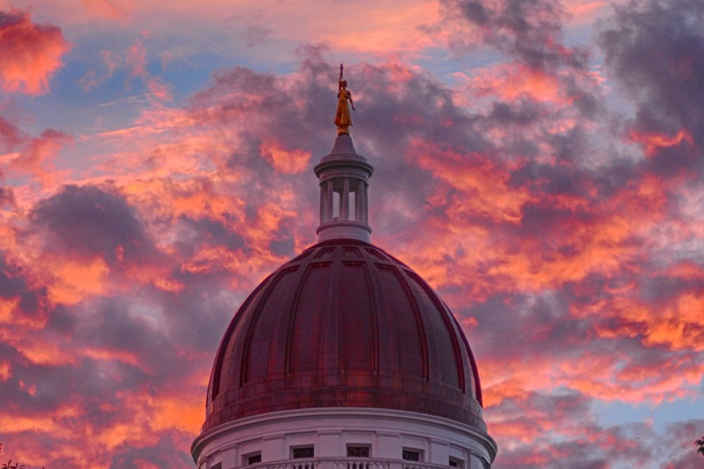 Clouds glow behind the Lady of Wisdom statue on top of the Maine State House dome during a sunset last summer. Cross-party discussions are happening inside as legislators prepare for the inevitable fight over the two-year budget that is required to be passed by July 1.