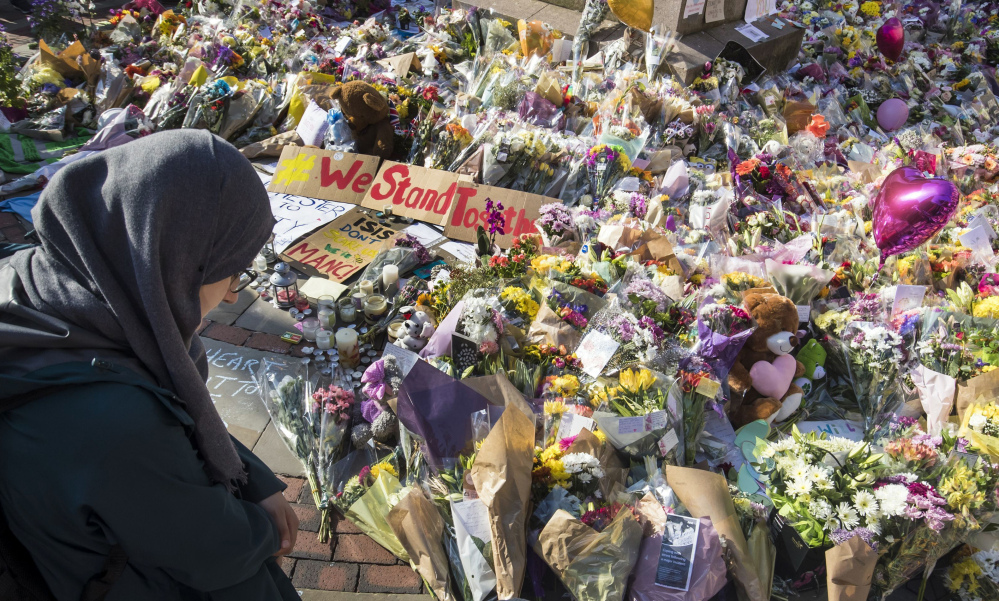 A woman looks at the floral tributes and messages left for the victims of the concert blast, during a vigil at St Ann's Square in central Manchester, England, on Wednesday.