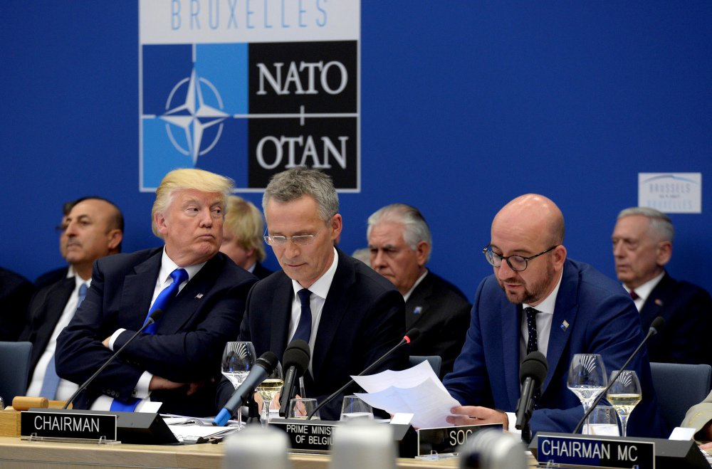 President Trump, left, sits next to NATO Secretary General Jens Stoltenberg, centre, as Belgian Prime Minister Charles Michel, right, delivers a speech, during the NATO summit of heads of state and government at the NATO headquarters in Brussels on Thursday.