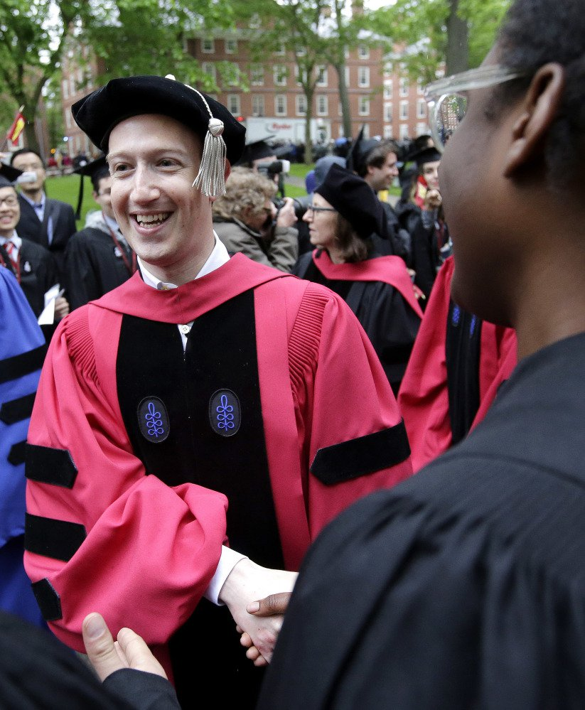 Facebook CEO and Harvard dropout Mark Zuckerberg greets graduating students as he walks in a procession though Harvard Yard.