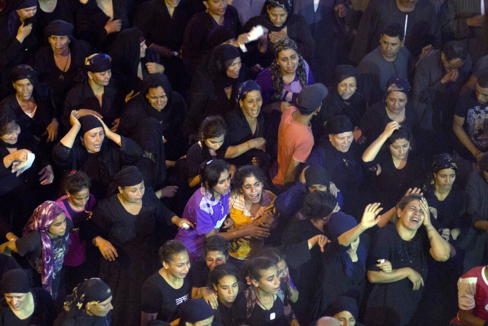 Relatives of Coptic Christians killed in a bus attack mourn at a funeral service at Abu Garnous Cathedral in Minya, Egypt, on Friday.