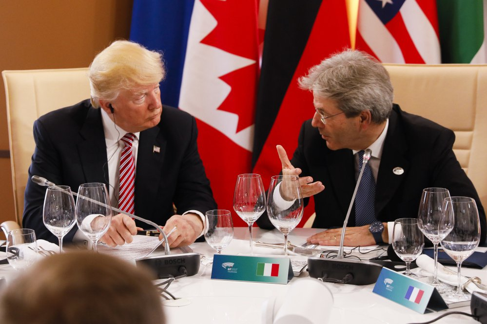 President Trump listens to Italian Prime Minister Paolo Gentiloni as they sit around a table during the G7 Summit in Taormina, Sicily.