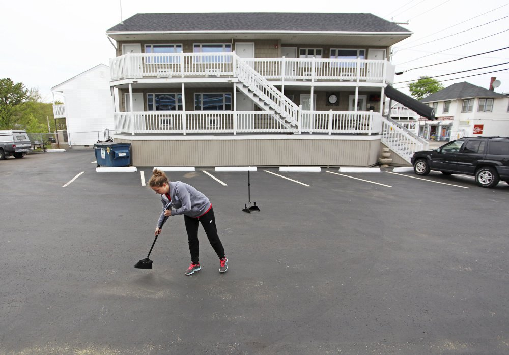 Marija Bralovic, who came from Serbia to work in Maine, sweeps the parking lot at the Green Dolphin Motel in Old Orchard Beach on Thursday in preparation for opening day Friday. Low unemployment and changes to a federal visa program are causing staffing shortages for some of the state's hospitality businesses.