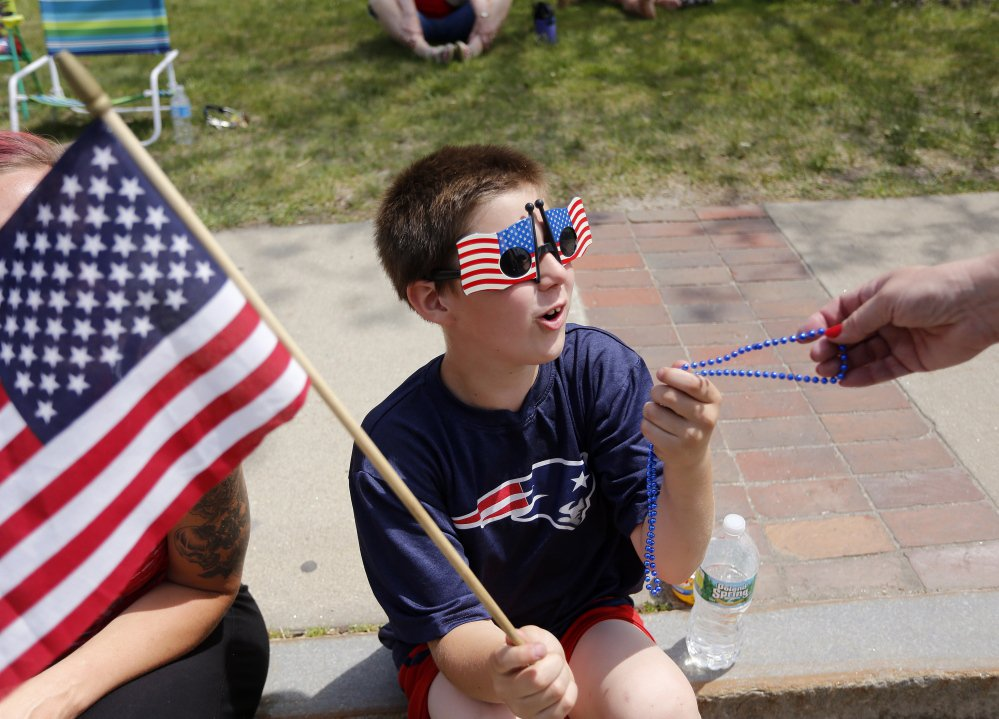 Kevin Woods, 8, of Old Orchard Beach is given beads by a marcher at the Old Orchard Beach Memorial Day parade.