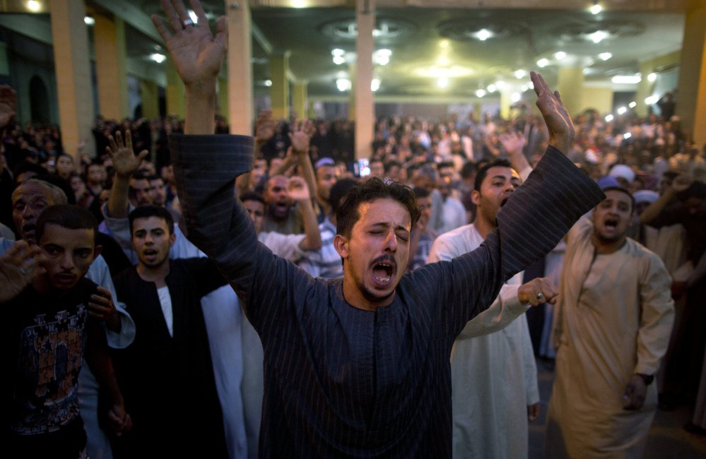 Coptic Christians shout slogans during a funeral service for victims of a bus attack in Minya, Egypt, on Friday. Egyptian officials say masked gunmen killed 29 people.