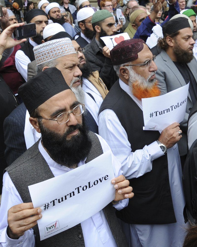 Members of the British Muslim Forum with religious leaders from Christian and Jewish faiths pay their respects to victims of last week's bombing, at St Ann's Square in Manchester, England, on Sunday.