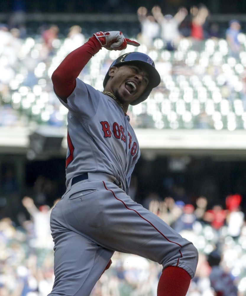 Boston outfielder Mookie Betts reacts as he rounds first after hitting a three-run home run in the ninth inning against the Brewers on Thursday in Milwaukee.