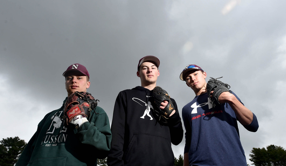 Nokomis pitchers Cody Rice, left, Matthew Dyer, center, and Joshua Perry stand on their mound during practice Thursday.