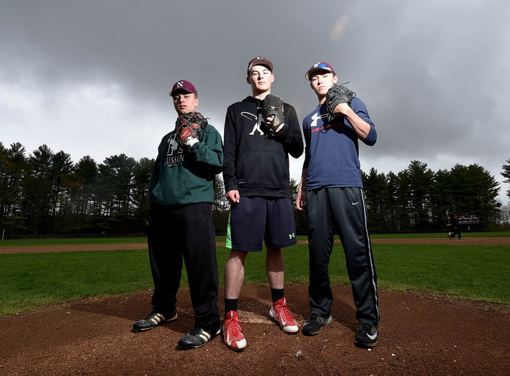 Nokomis pitchers Cody Rice, left, Matthew Dyer, center, and Joshua Perry stand on their mound during practice Thursday