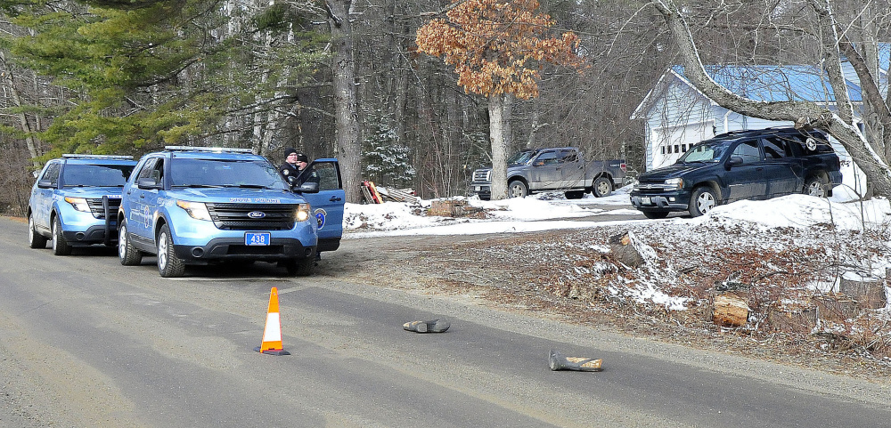 Two Maine State Troopers consult outside a home on the Winnecook Road in Burnham while investigating the reported death of a woman on April 2. A pair of winter boots lie in the roadway in foreground.