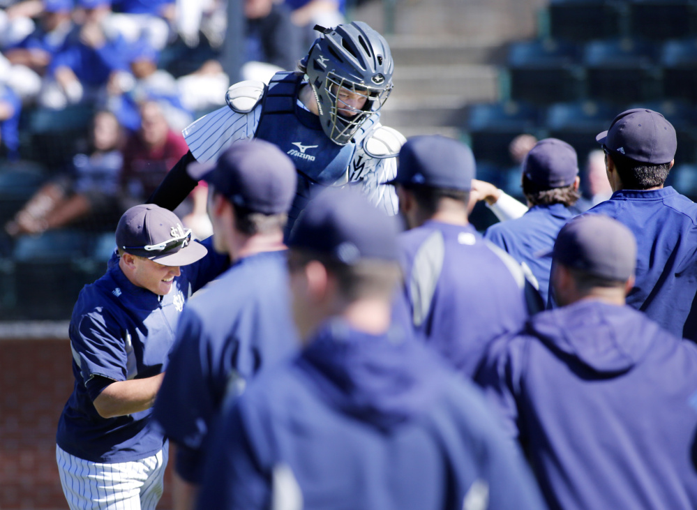 Kip Richard is met by University of Southern Maine teammates after they beat Eastern Connecticut State on Friday.