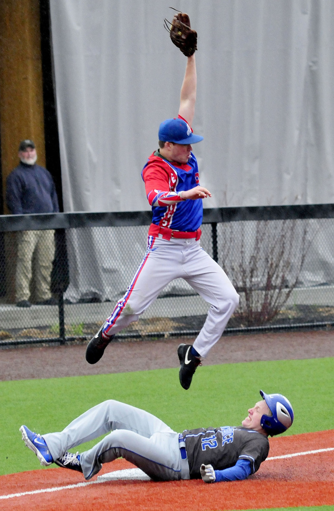 Lawrence baserunner Brandon Hill makes it to third base as Messalonskee's Cam Goff goes airborne to haul in a ball during a game Monday at Colby College.