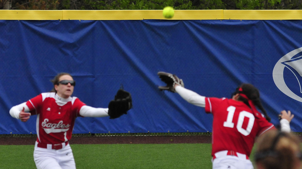 Messalonskee's Danielle Holt, left, and Kate Pino run to catch a fly ball during a Kennebec Valley Athletic Conference Class A game against Lawrence on Monday at Colby College in Waterville.