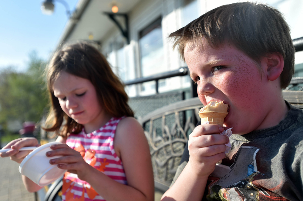 Benjamin  Finnimore, 9, right, prefers his ice cream in a cone whereas his sister Melissa prefers it in a dish on hot days at the North Street Dairy Cone in Waterville on Thursday. The temperature recorded at the Waterville airport hit 91 degrees Thursday, beating the previous record of 88 degrees in 1977.