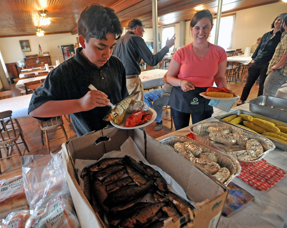 Fernando Cuares and Darcy Dow help themselves to smoked alewives and lobster at the annual alewife festival dinner at the Benton Grange on May 15, 2015.