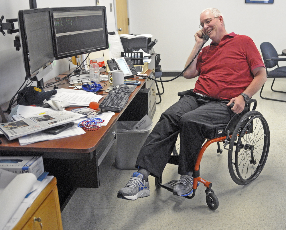 Augusta Police Chief Robert Gregoire does leg lift exercises while talking on the phone in his wheelchair on July 9, 2015. The Maine Human Rights Commission ruled Monday that there were no reasonable grounds to believe he was discriminated against when his parking lot wasn't immediately plowed after a big snowstorm in December.