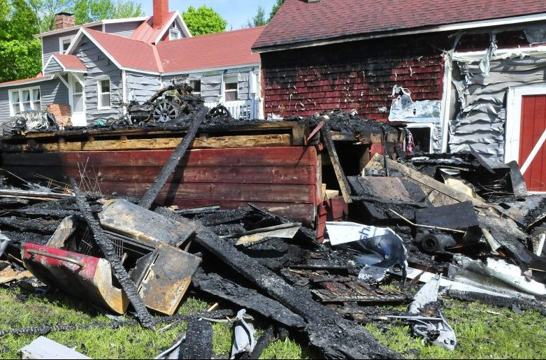 A propane cooking grill, foreground, lies in a pile of burned debris Tuesday from a garage that burned Monday evening at the David McKeage residence on the Bellsqueeze Road in Clinton. A car, truck and new siding on a nearby barn were damaged and a three-wheel motorcycle was destroyed after a passerby spotted smoke and flames shortly after McKeage had finished grilling dinner.