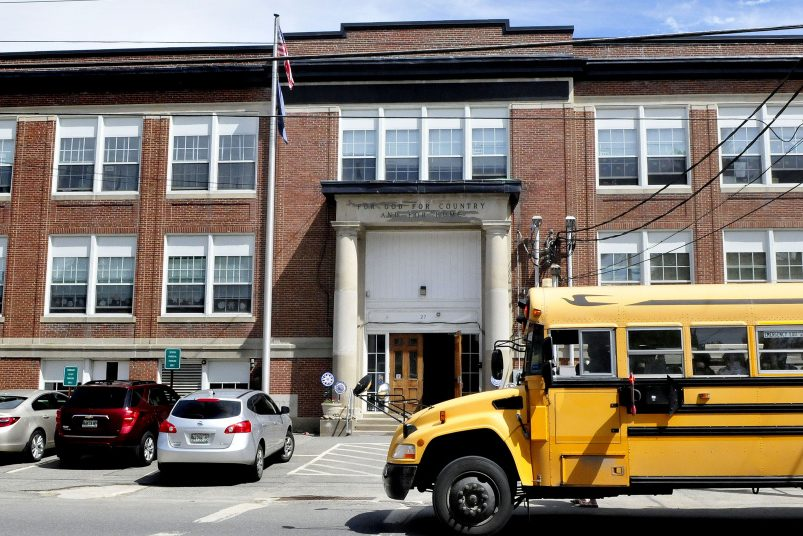 Students board a school bus parked in front of the Albert Hall School in Waterville on May 23. Some residents are calling for the closure of the school as soon as possible to save money amid a declining student population, but officials say the process would take about three years.