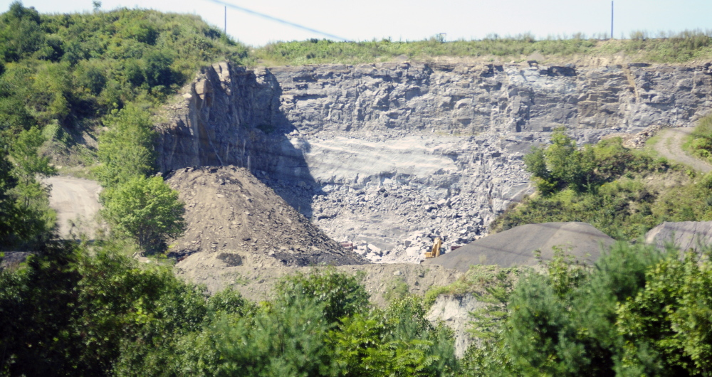 The McGee rock blasting pit is seen from east side of Kennebec River on Sept. 4, 2015, in Augusta. Planning Board members have delayed action on a license for the pit so they have time to consult an expert and experience the blasting for themselves.