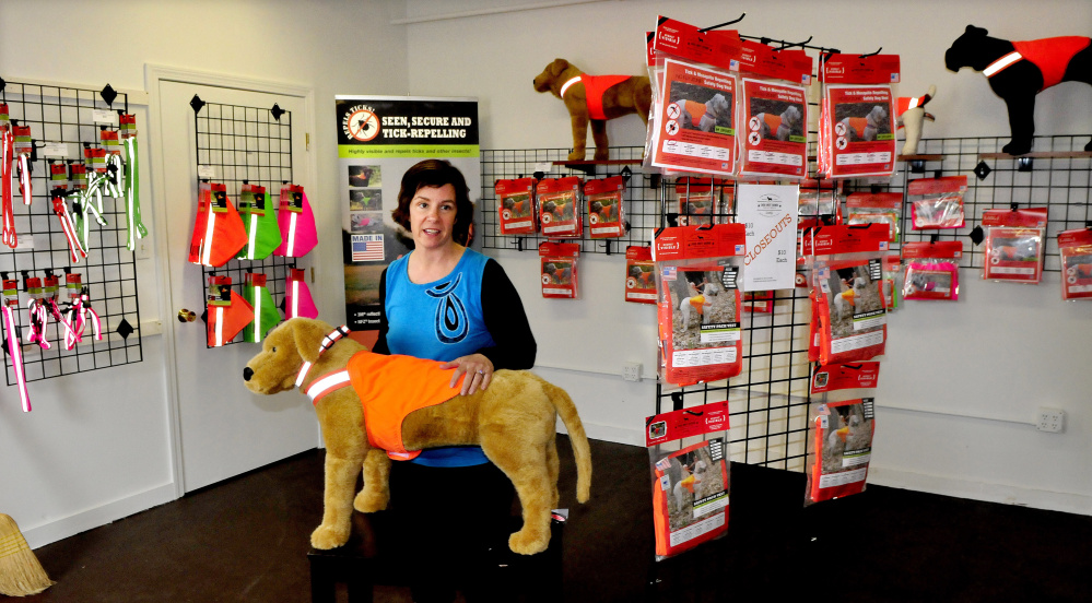 Owner Julie Swain fits a safety vest on a dog mannequin Wednesday beside many products sold at the new Dog Not Gone factory outlet store inside the Maine Stitching Specialties company in Skowhegan.