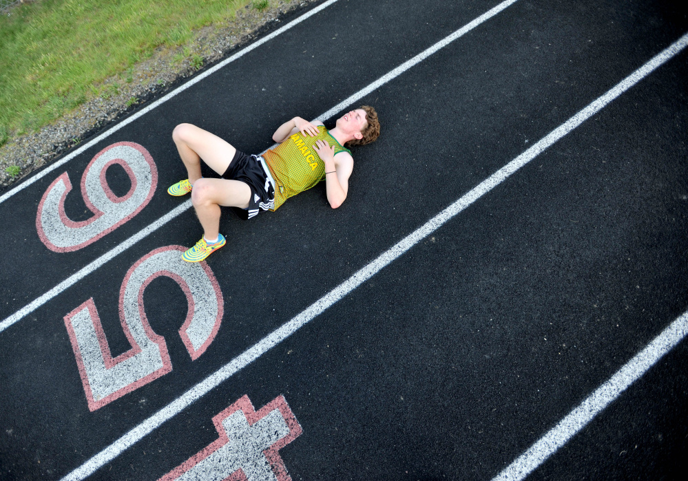 Winslow's Ben Smith gets some rest on the track during practice Wednesday at the high school.