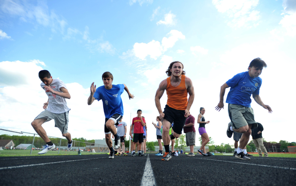 Winslow's Jacob Bisson, left, Spencer Miranda, left center, Ryan Fredette, right center, and Jake Warn work out during track practice Wednesday at Winslow.