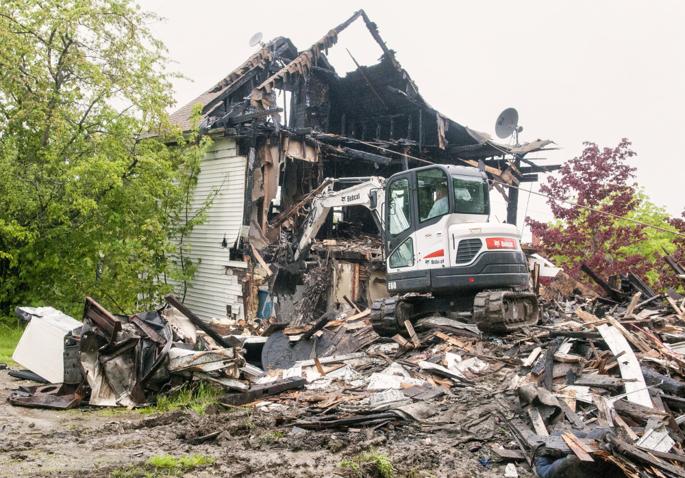 Staff photo by Joe Phelan Driving a Bobcat excavator, Bob Anair demolishes 34 Main St. on Friday in downtown Richmond. The house across the street from the Old Goat Pub had been heavily damaged by a fire last Christmas.
