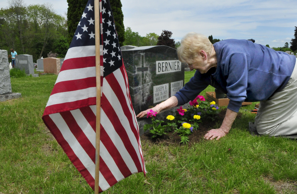 Dorothy Bernier, of Waterville, plants flowers Wednesday around the grave of her husband, Joseph, who was wounded while serving in the U.S. Marines, at St. Francis Catholic Cemetery in Waterville.