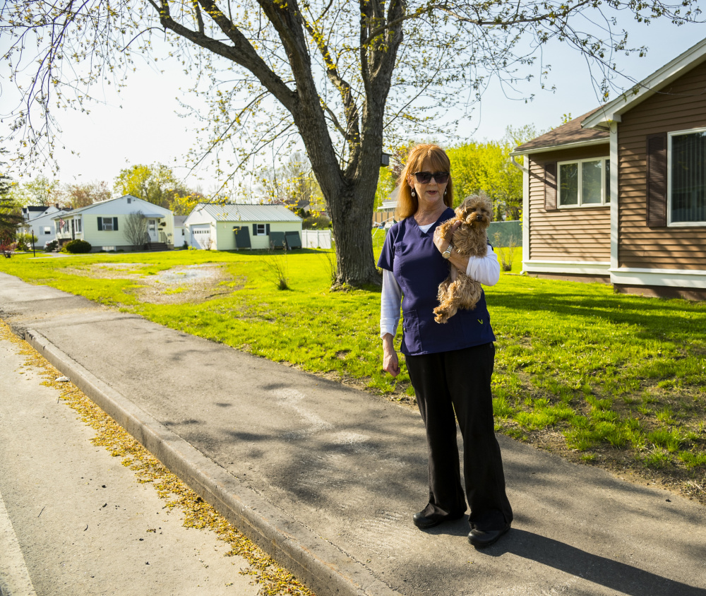 Jacquelyn Cyr, of Windsor Avenue in Augusta, stands with her dog Poppy on Wednesday on a new sidewalk in front of her house. She said that the sidewalk, which was replaced two years ago, is causing standing water to appear on lawns in her neighborhood.