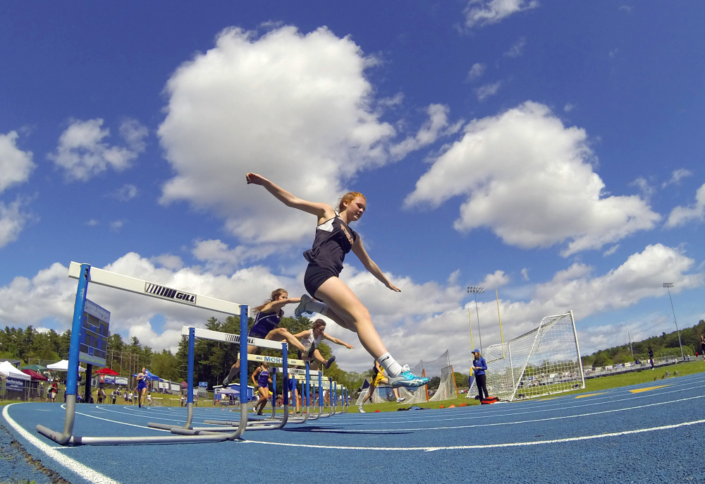 Winslow's Grace Smith runs the 300 meter hurdles at the Kennebec Valley Athletic Conference track and field championships Saturday at McMann Field in Bath.