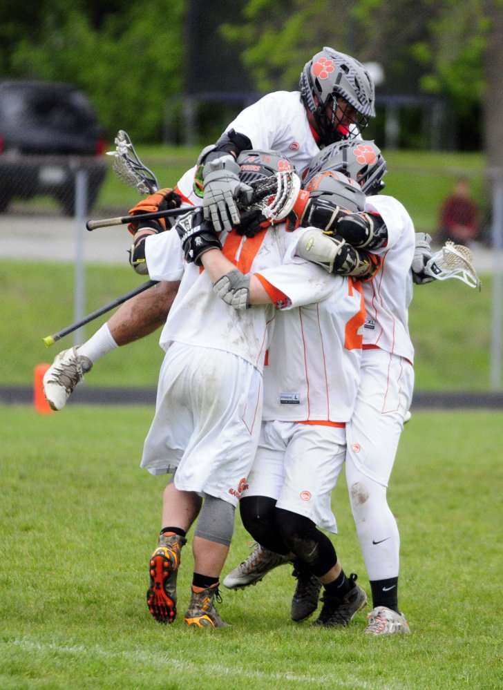 Members of the Gardiner boys lacrosse team celebrate an overtime victory Tuesday over Messalonskee at Hoch Field in Gardiner.