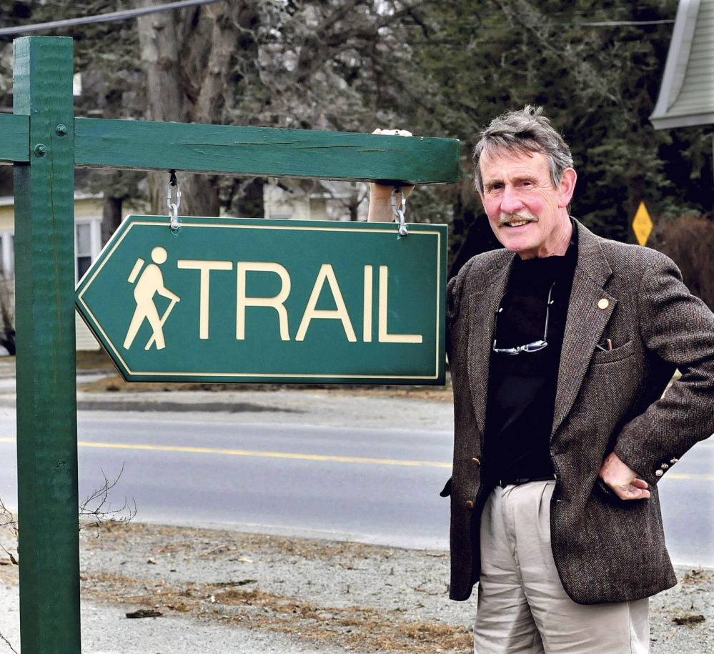 Peter Garrett, a director of the Kennebec Messalonskee Trails organization, beside a sign along the 40-mile network of trails in 2014, invites surrounding communities to take part in the annual National Trails Day walk on Saturday in the spirit of cooperation and civility.