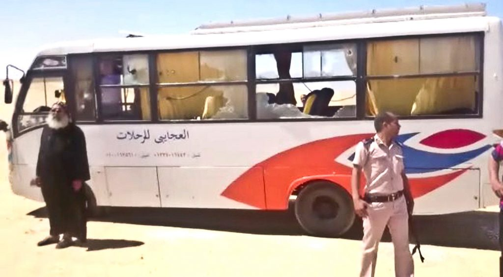 A policeman and a priest stand next to a bus after it was stormed by gunmen in Minya, Egypt, on Friday. Egyptian officials say dozens of people were killed and wounded in the attack on a bus carrying Coptic Christians, including children, south of Cairo.
