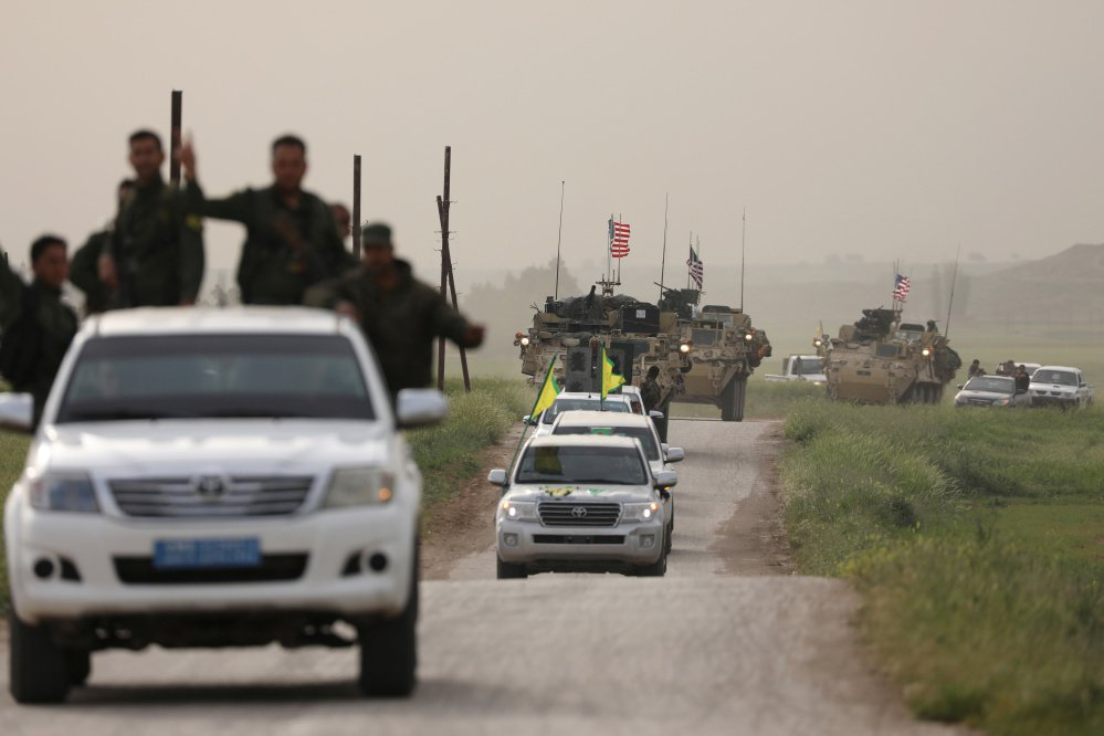 Kurdish fighters from the People's Protection Units head a convoy of U.S military vehicles in the town of Darbasiya, next to the Turkish border in Syria, in April.