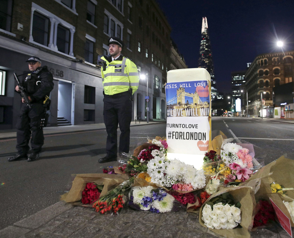 Police officers stand guard next to floral tributes in London near the scene of Saturday's attack by men who rammed some people with a van and stabbed others.