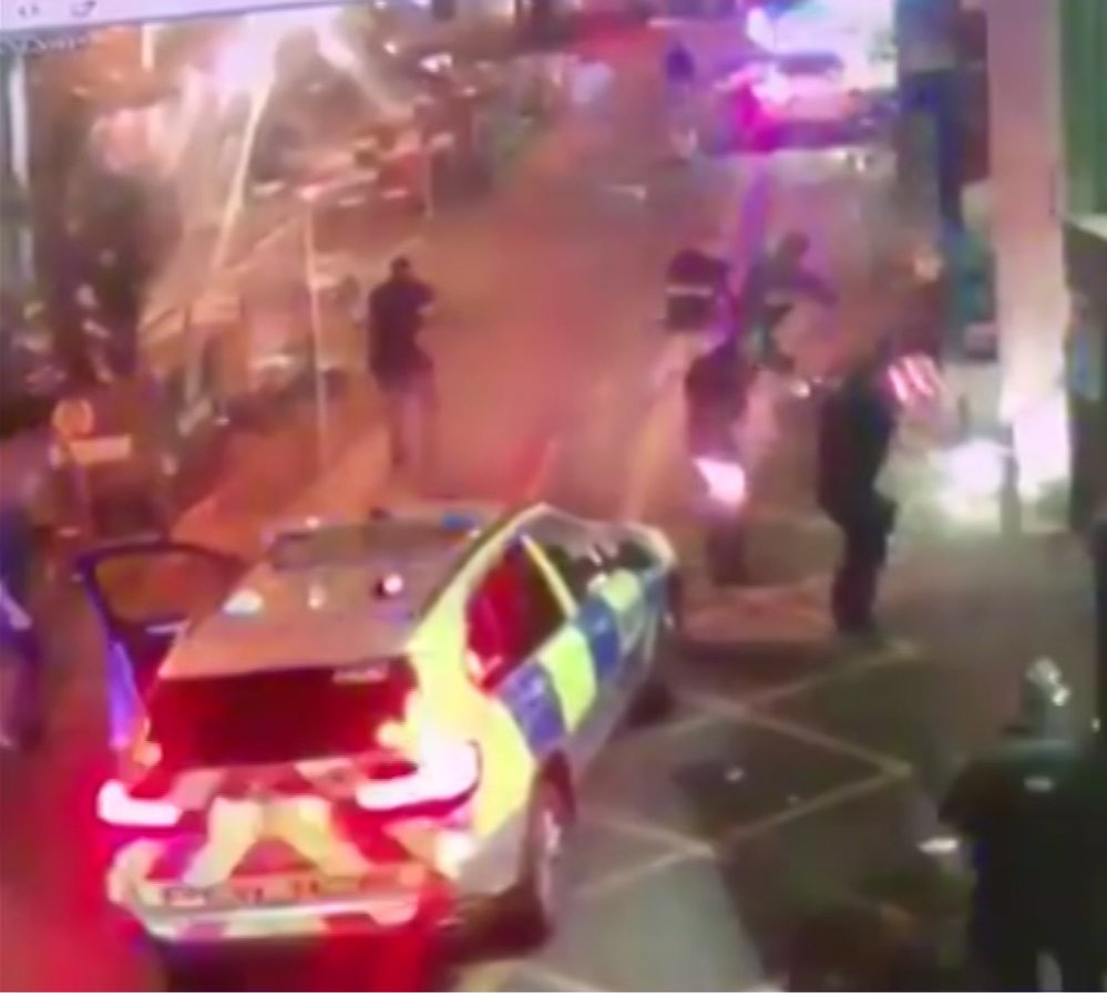 In this image taken from video which emerged on social media, shows police as they surround an attacker on the ground at right, during the  attack in Borough Market in southeast London on June 3. The dramatic video footage has been released showing the moment that armed police swooped into a busy London market area to stop an attack in just eight minutes.
