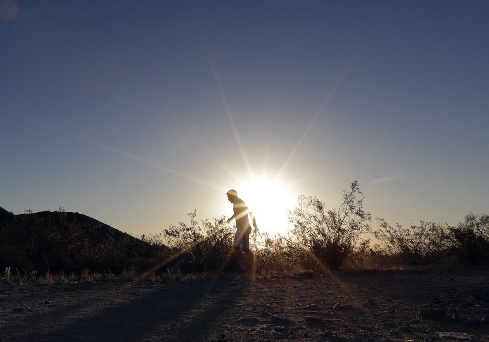 A man runs through South Mountain Park in Phoenix at sunrise to avoid the excessive heat Friday. A record heat wave is rolling into Arizona, Nevada and California.