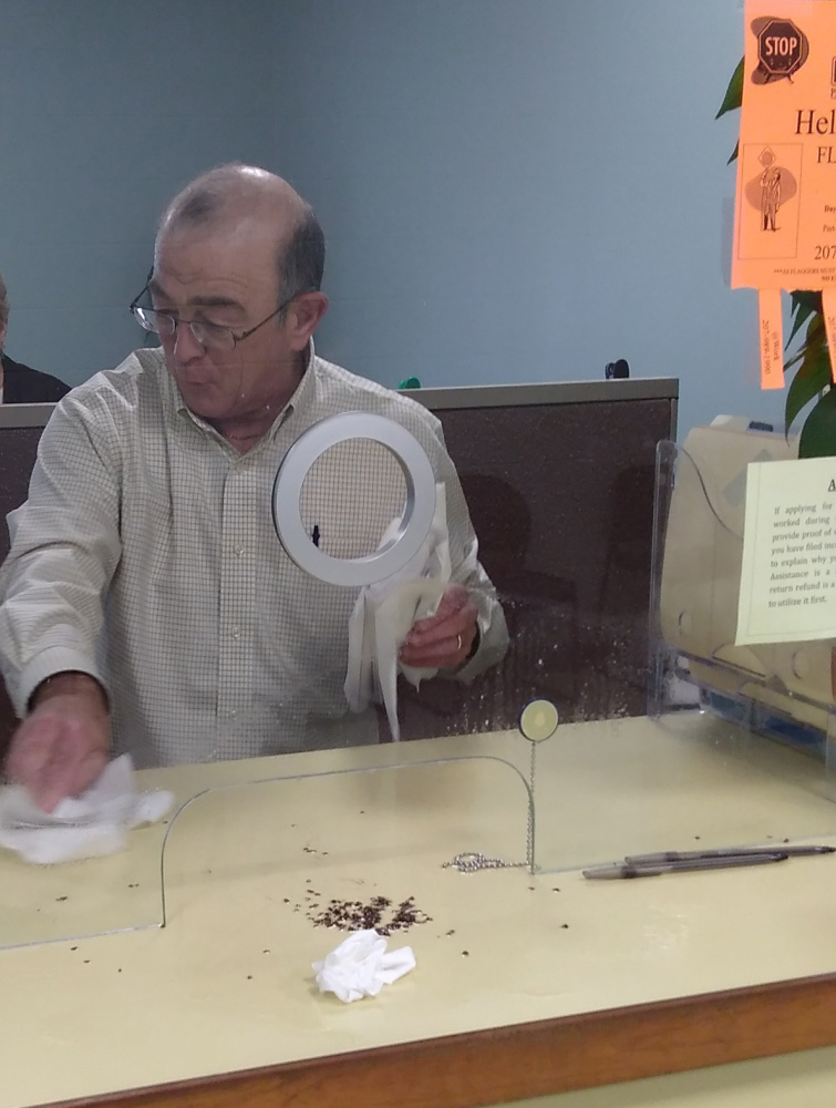 Ralph St. Pierre, Augusta's finance director and assistant city manager, picks up bedbugs that a disgruntled visitor reportedly unleashed Friday afternoon at Augusta City Center.