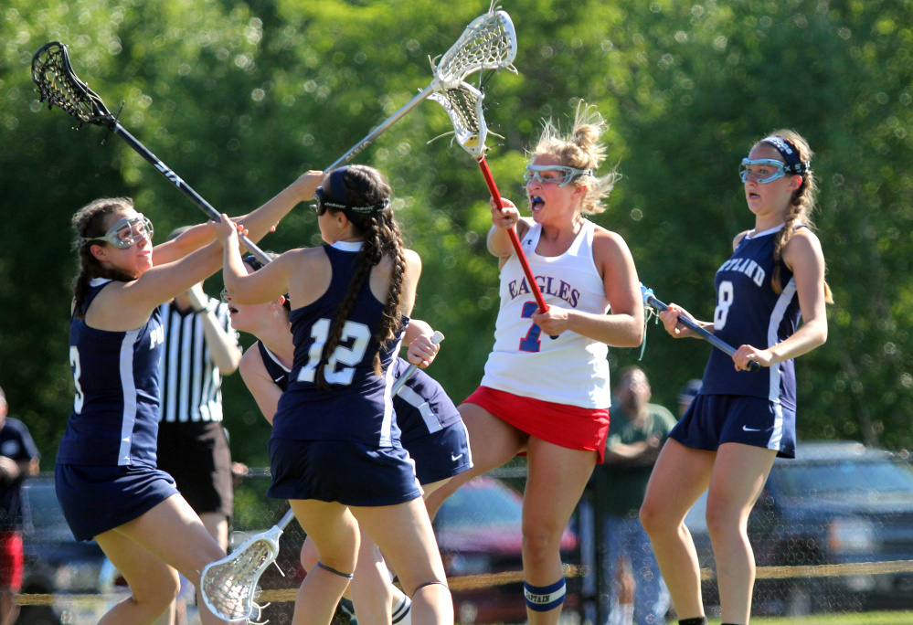 Messalonskee's Lydia Dexter fires a shot past Portland defenders Elena Clifford, left, Charlie Green (12) and Sarah Bryan (8) during the first half of a Class A North girls lacrosse quarterfinal Wednesday at Thomas College.