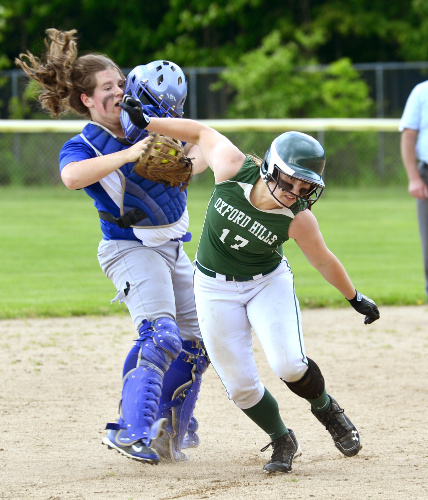 Lawrence catcher Haley Holt gets her face mask knocked off while chasing Oxford Hills Hannah runner Kenney between second and third base during a Class A North semifinal game Saturday in South Paris.