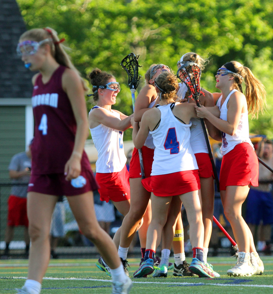The Messalonskee High School girls lacrosse team celebrates its 7-6 overtime win over Windham in the Class A North championship game Wednesday at Thomas College.